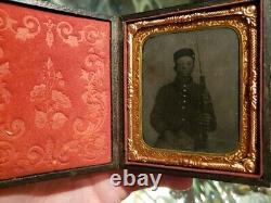 Very dark civil war tintype of young soldier with very unusual weapon armed case